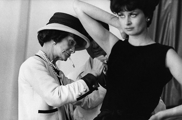 Coco Chanel adjusts the armhole of a model's dress with an assistant. ---1961 Paris
